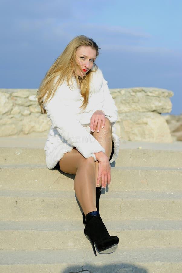 La bella ragazza in un cappotto di pelliccia bianco immagine stock