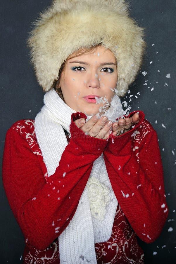 La bella ragazza in un cappuccio scarica la neve dalle mani immagine stock libera da diritti