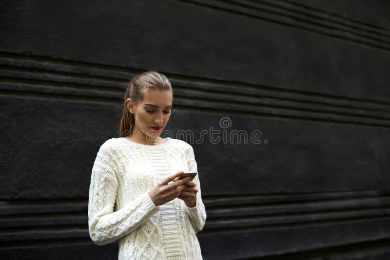 La bella ragazza in un maglione leggero che sta il fondo vicino di promozione per il vostro annuncia fotografie stock libere da diritti