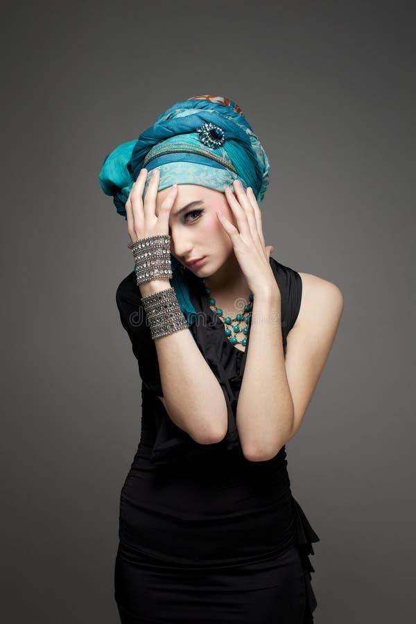 La bella ragazza in un turbante e nei gioielli immagini stock libere da diritti