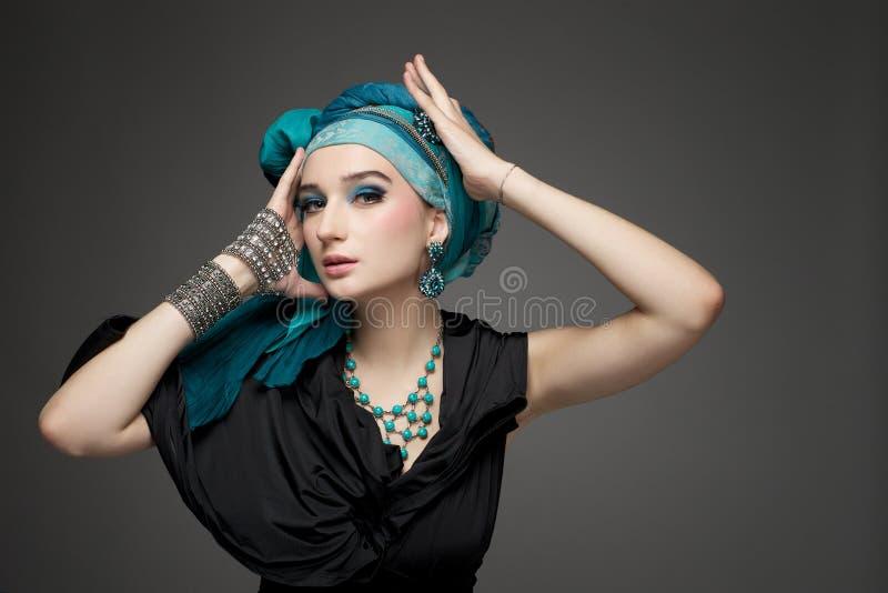 La bella ragazza in un turbante e nei gioielli immagini stock