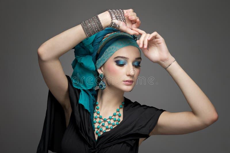 La bella ragazza in un turbante e nei gioielli fotografia stock