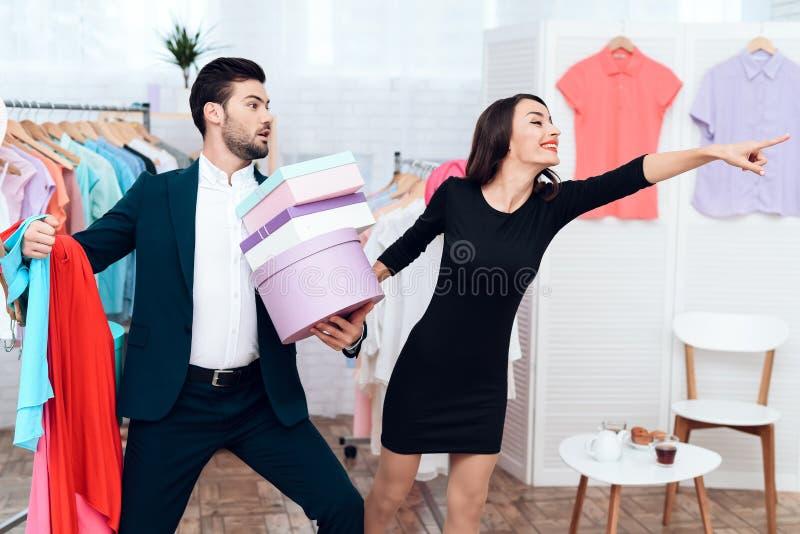 La bella ragazza in un vestito e un uomo attraente in vestito stanno comperando Sono in una sala d'esposizione leggera immagine stock libera da diritti