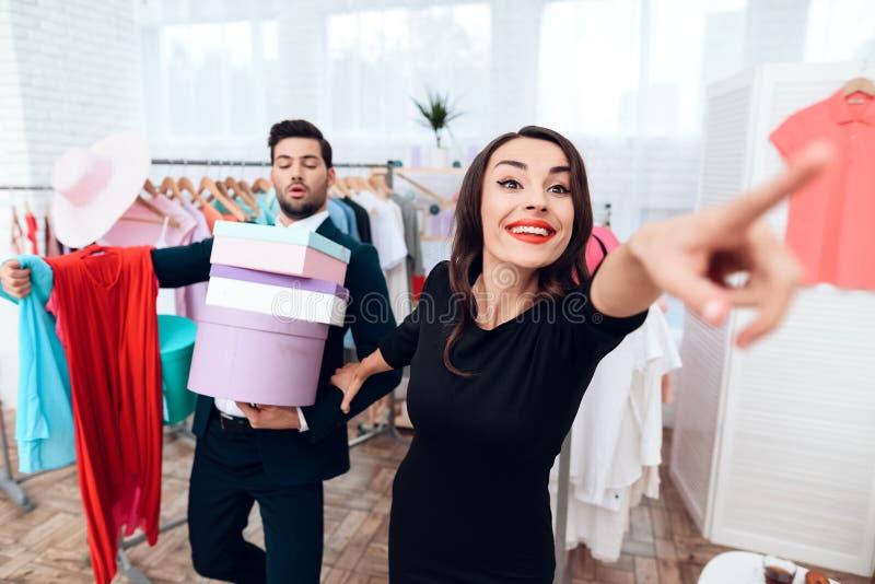 La bella ragazza in un vestito e un uomo attraente in vestito stanno comperando Sono in una sala d'esposizione leggera fotografie stock libere da diritti