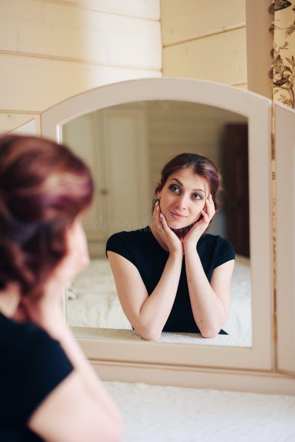 La bella ragazza in un vestito nero si siede davanti ad uno specchio d'annata, riflesso in tre specchi fotografia stock