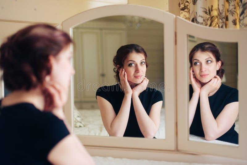 La bella ragazza in un vestito nero si siede davanti ad uno specchio d'annata, riflesso in tre specchi immagini stock libere da diritti