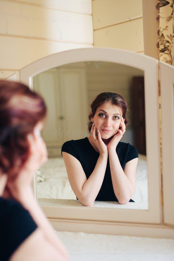 La bella ragazza in un vestito nero si siede davanti ad uno specchio d'annata, riflesso in tre specchi fotografia stock libera da diritti