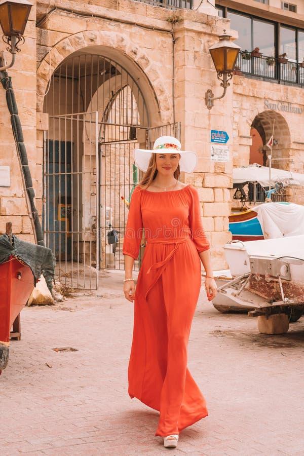 La bella ragazza in un vestito rosso che cammina in barche si è messa in bacino sull'isola di Malta fotografia stock