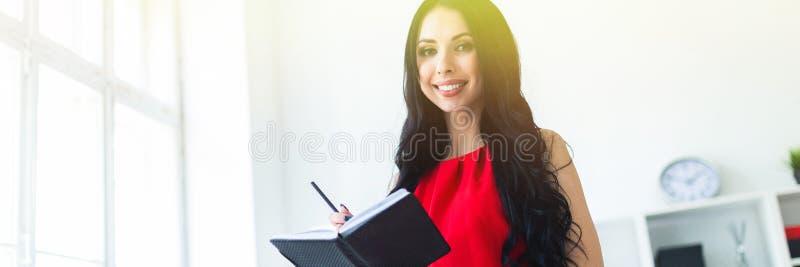 La bella ragazza in un vestito rosso sta stando nell'ufficio e sta tenendo un taccuino e una matita immagini stock libere da diritti
