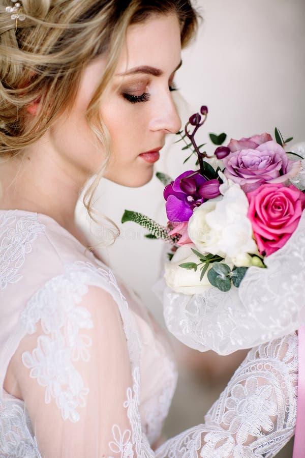 La bella ragazza in vestito di pizzo tenero con il mazzo fiorisce le peonie in mani che stanno contro il fondo floreale nel negoz immagini stock libere da diritti