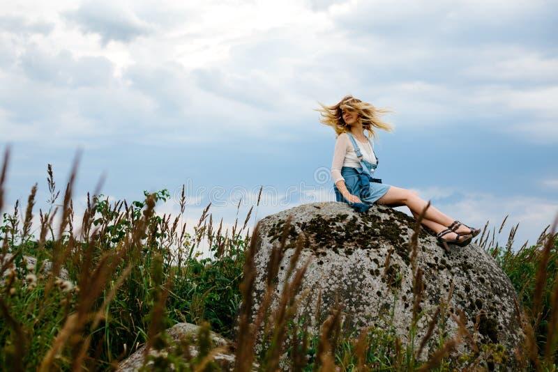 la bella roccia della ragazza si siede immagini stock
