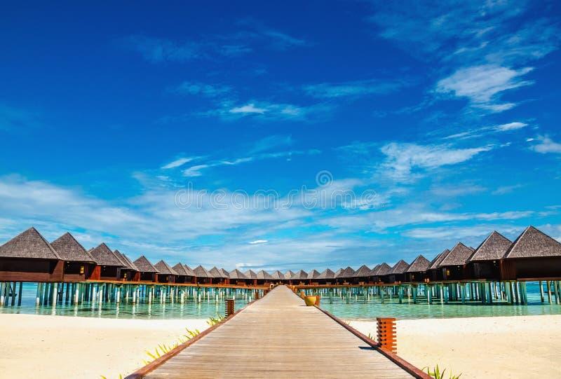 La bella spiaggia esotica ed il ponte di legno a stupire i bungalow esotici su turchese innaffiano immagini stock