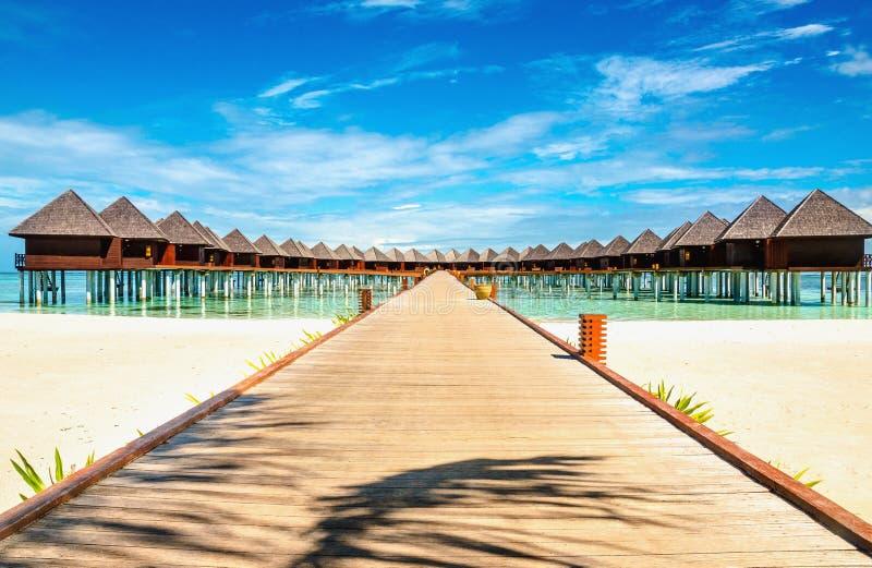 La bella spiaggia esotica ed il ponte di legno a stupire i bungalow esotici su turchese innaffiano immagini stock libere da diritti