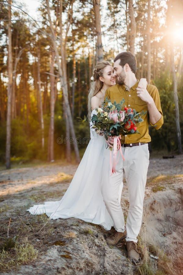 La bella sposa abbraccia il suo sposo dalla spalla La passeggiata di nozze in una persona appena sposata della foresta A se esami immagine stock