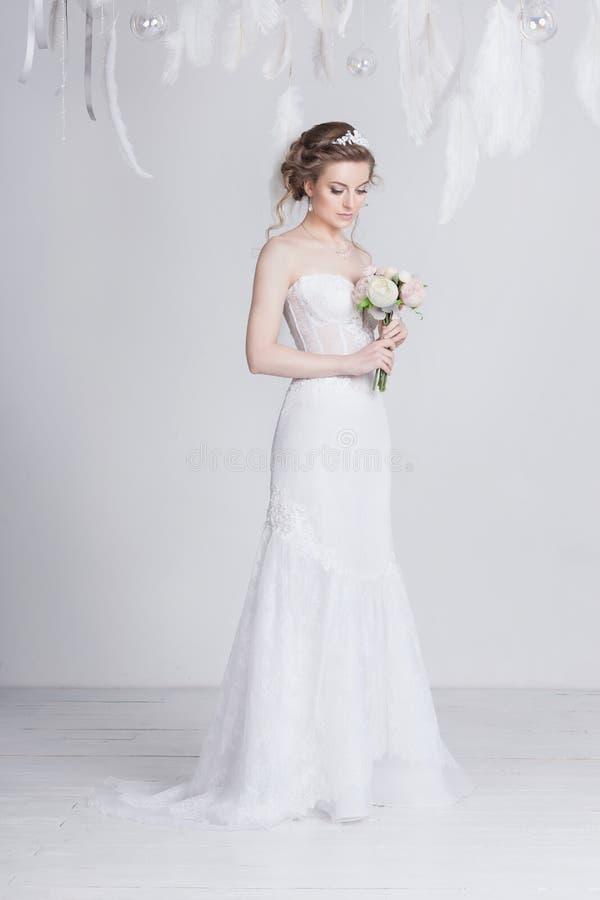 La bella sposa con pizzo fiorisce in suoi capelli biondi scuri splendidi Alti acconciatura, trecce e riccioli di nozze immagine stock libera da diritti