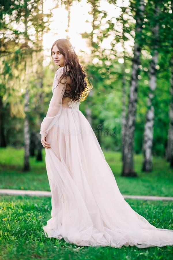 La bella sposa della ragazza castana all'abito nuziale delicato del boudoir di pizzo e Tulle nel colore beige è all'aperto, in un immagine stock libera da diritti