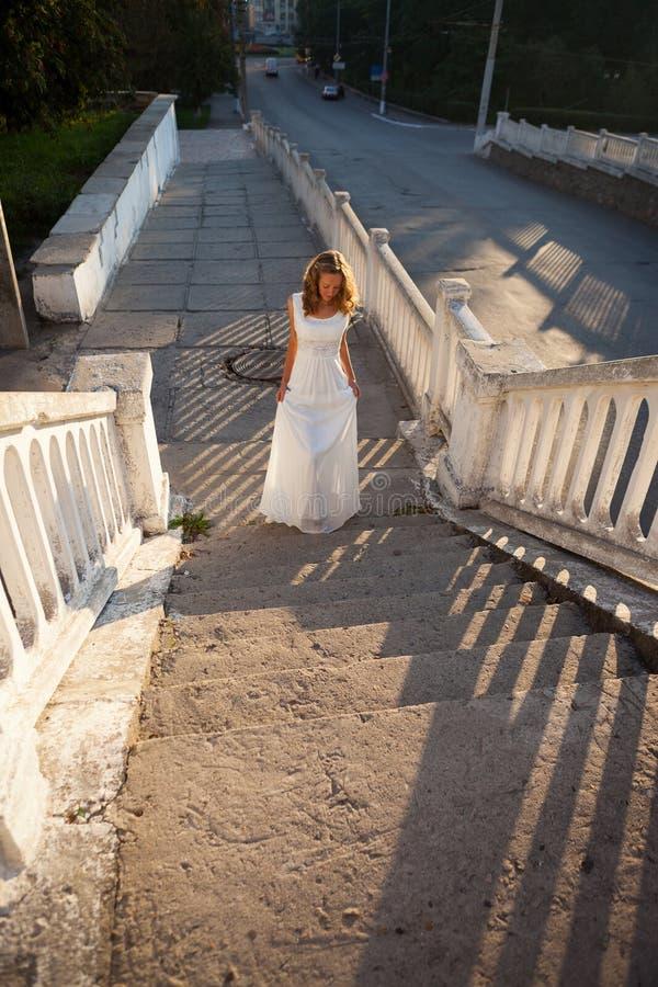 La bella sposa della ragazza in un vestito bianco aumenta sui provvedimenti concreti fotografie stock libere da diritti