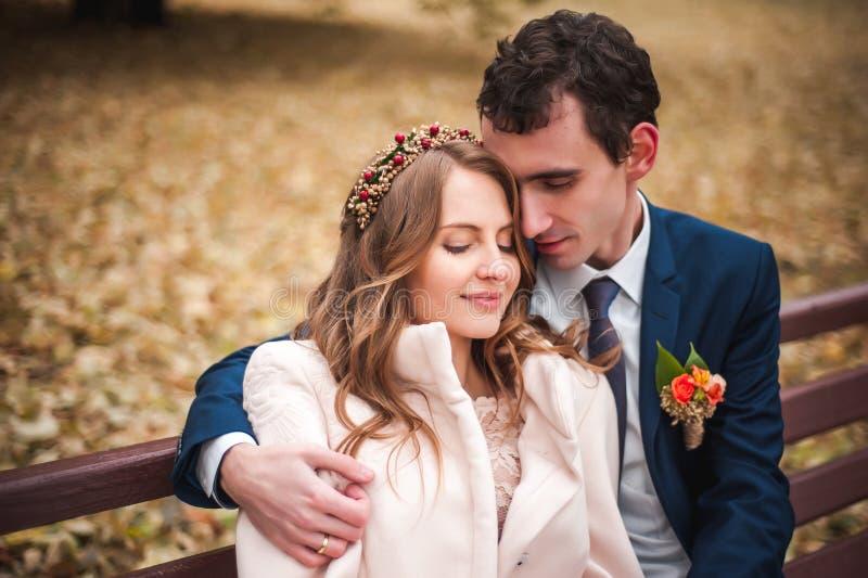 La bella sposa e lo sposo bello che si siedono su un banco in autunno parcheggiano immagine stock libera da diritti