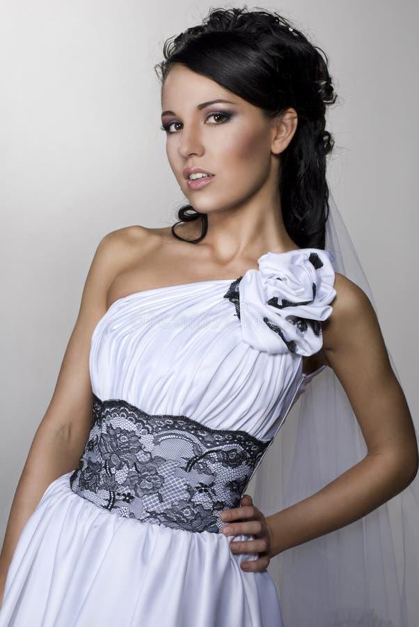 La bella sposa sta levandosi in piedi in vestito da cerimonia nuziale immagine stock