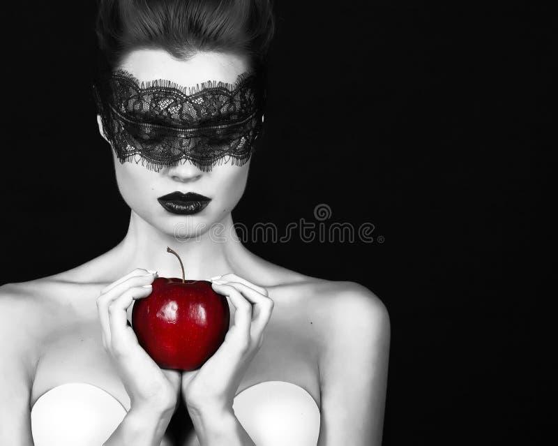 La bella strega della strega della ragazza con un pizzo del nero della fasciatura che tiene il fascino magico della mela matura h fotografia stock libera da diritti