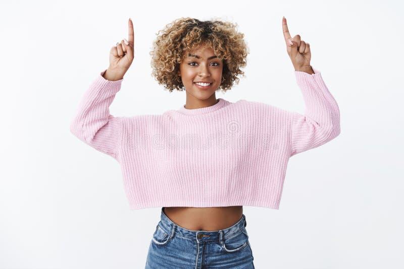 La bella studentessa dalla carnagione scura adatta con capelli giusti in maglione potato alla moda caldo che solleva le mani indi immagine stock