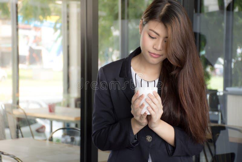 La bella tazza di tè asiatica della tenuta della ragazza sta godendo di con tempo della rottura fotografia stock libera da diritti