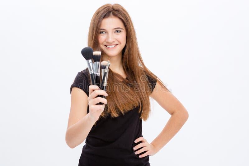 La bella tenuta allegra della giovane donna compone le spazzole fotografia stock libera da diritti