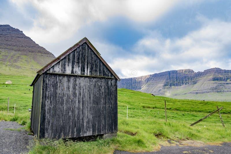 La bella vista del nero ha sbiadito il granaio di legno con erba verde di SH fotografia stock libera da diritti