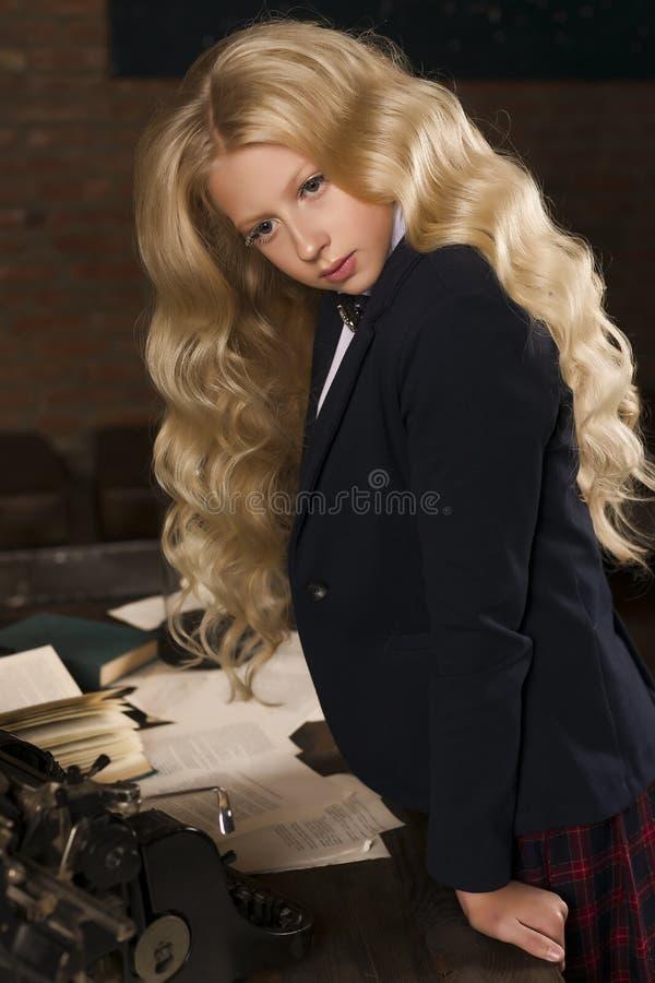 La belle écolière blonde bouclée aux cheveux longs reste fatigué à a photos stock