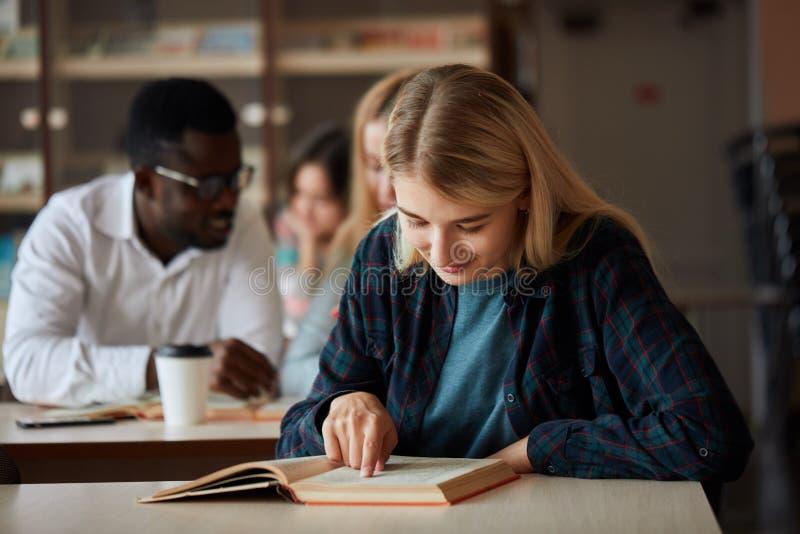 La belle étudiante heureuse blonde de femme suit des classes d'université à l'intérieur photos stock