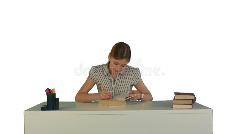 La belle étudiante a lu le livre sur le fond blanc d'isolement image libre de droits