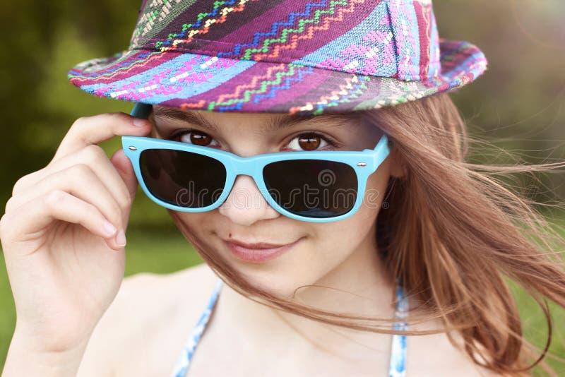 La belle étudiante naturelle d'écolière de petite fille de beauté porte des lunettes s'habillent, jour d'été ensoleillé lumineux  image stock