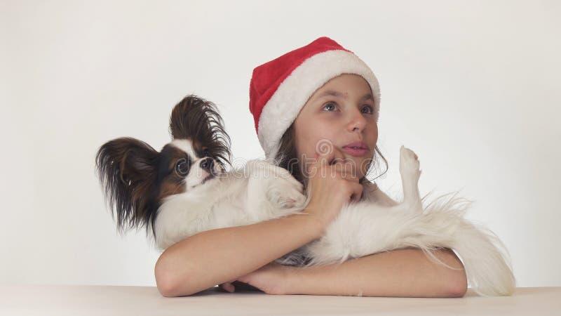 La belle adolescente dans le chapeau de Santa Claus étreint heureusement son chien et sembler étonnée sur le fond blanc images stock