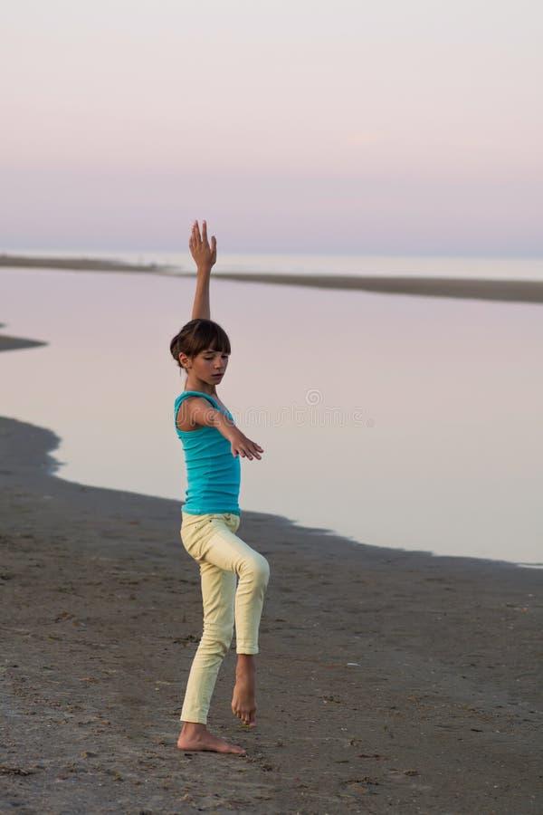 La belle adolescente est sur le point de faire une roue gymnastique de foret sur le fond de la mer au coucher du soleil, images stock