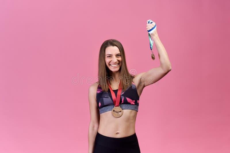 La belle athlète réussie de fille sur le fond d'isolement montre la victoire, succès, médailles photos libres de droits