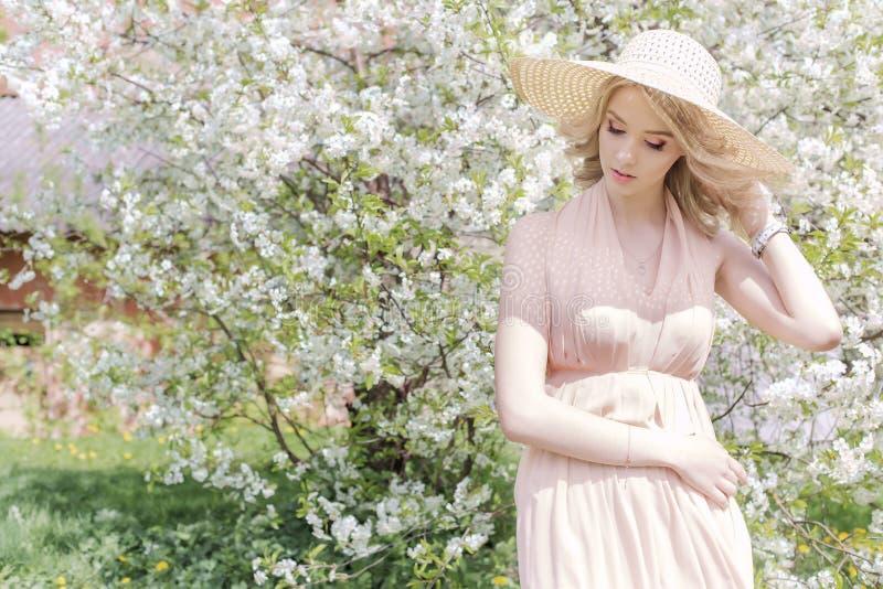 La belle belle fille douce dans un chapeau d'été avec un maquillage léger, avec de pleines lèvres marche dans le jardin de florai images libres de droits