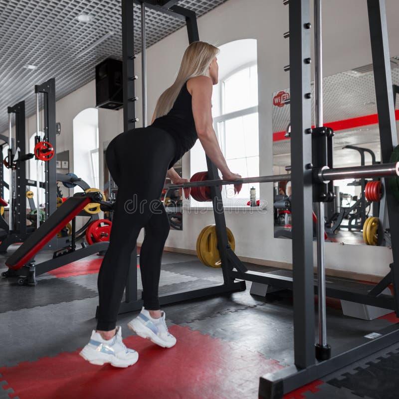 La belle blonde de jeune femme dans les vêtements de sport avec un beau corps mince se tient près d'un simulateur en métal dans u photos libres de droits