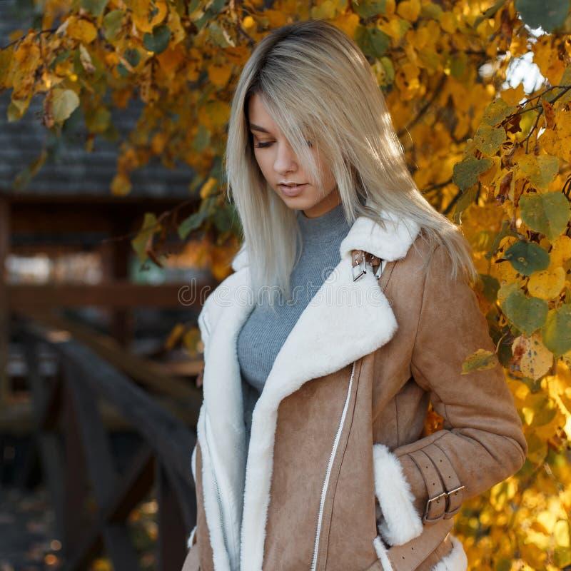 La belle blonde de jeune femme dans une veste élégante légère et un chandail gris se tient en parc regardant vers le bas photographie stock