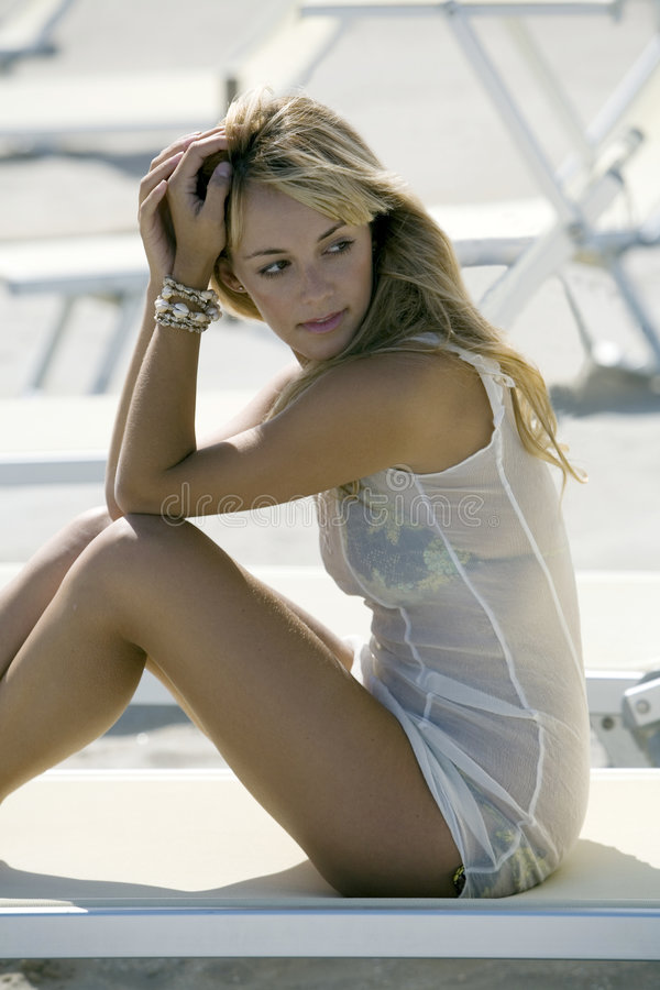 La belle blonde s'asseyent sur une présidence de paquet à la plage photo stock