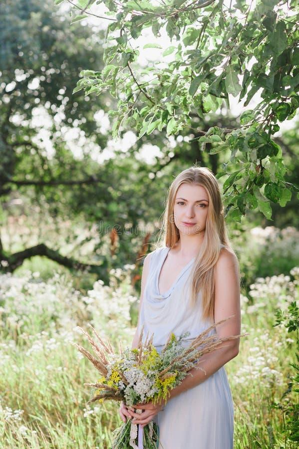 La belle blonde sur la nature avec un bouquet des fleurs image stock