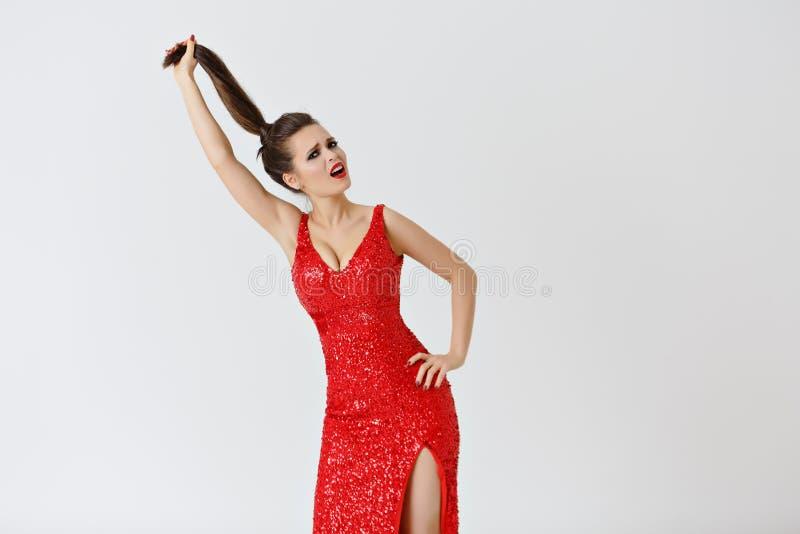 La belle brune aux cheveux longs dans la robe rouge tire ses cheveux goujon images stock