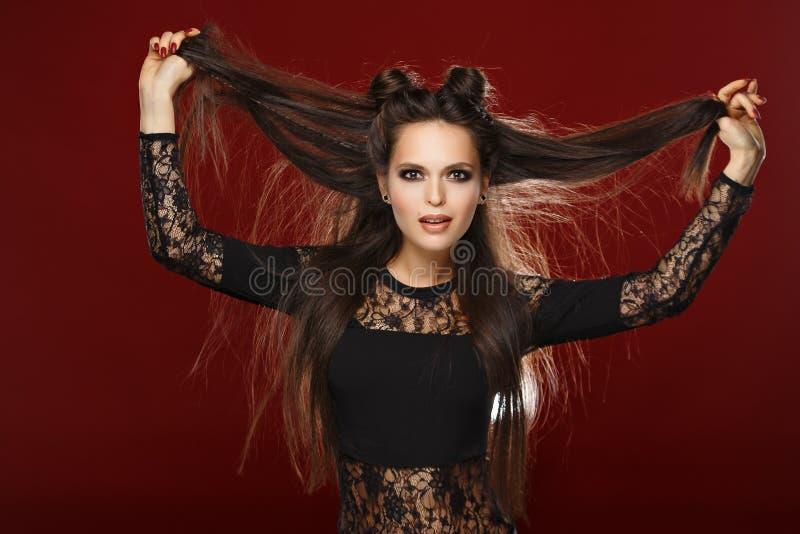La belle brune aux cheveux longs garde ses cheveux Studio, dos d'obscurité photo stock
