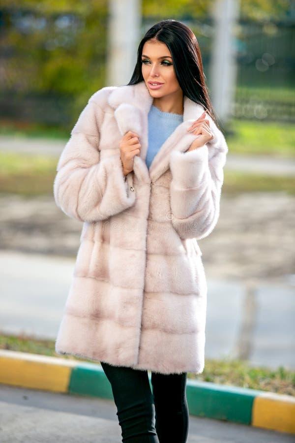 La belle brune dans un manteau de fourrure de couleur claire et des pantalons noirs se tient sur la rue un jour ensoleillé d'auto photo libre de droits