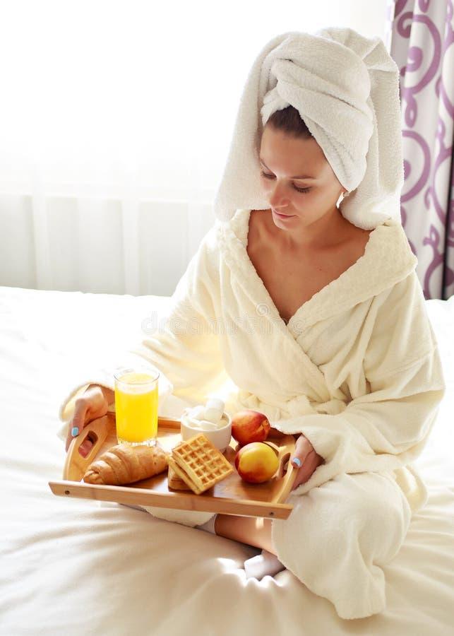 La belle brune dans une robe de chambre et un pull molletonné sur sa tête prend le petit déjeuner dans le lit images libres de droits