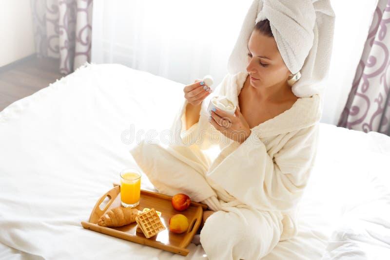 La belle brune dans une robe de chambre et un pull molletonné sur sa tête prend le petit déjeuner dans le lit photographie stock