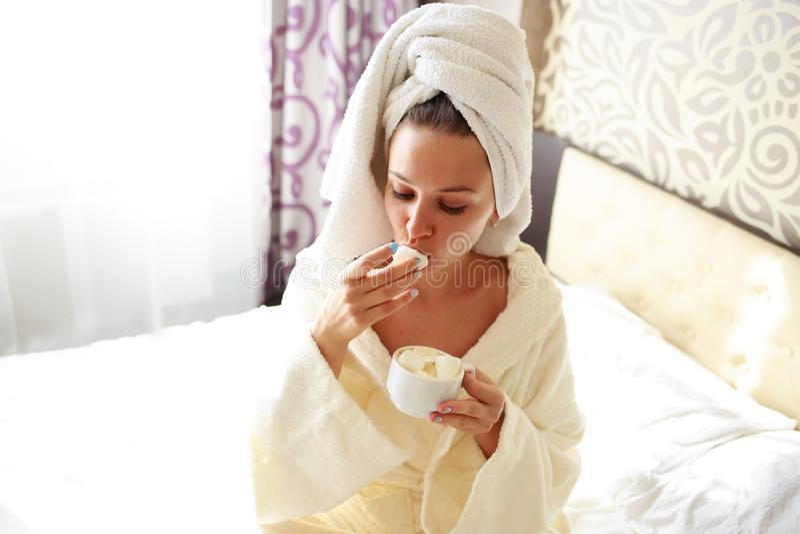 La belle brune dans une robe de chambre et un pull molletonné sur sa tête prend le petit déjeuner dans le lit photo stock