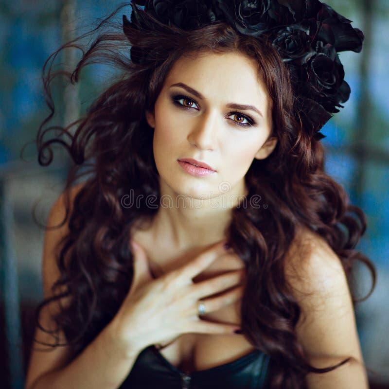 La belle brune sensuelle avec une guirlande de noir fleurit le sittin photo stock
