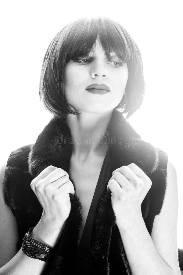 La belle brune tenant ses mains s'approchent de son visage et du regard en longueur photo libre de droits