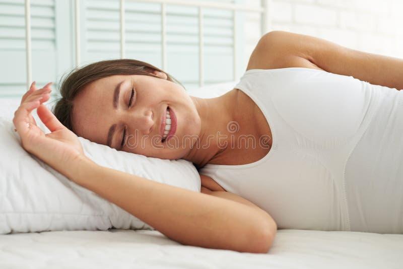 La belle brune a un bon sommeil dans son lit image libre de droits