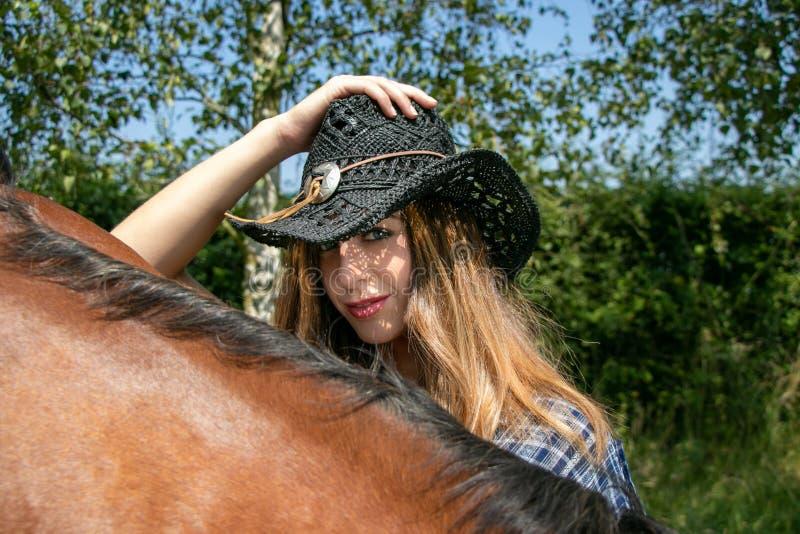 La belle cow-girl avec le chapeau et les yeux bleus regardent l'appareil-photo avec le cheval dans le forground images libres de droits